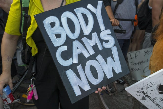 The Rockford City Council has approved a balanced 2021 budget that includes funds for the acquisition and maintenance of body-worn cameras. In this file photo, a demonstrator holds a sign demanding body cameras for police officers on Saturday, June 6, 2020, during a march through Rockford.