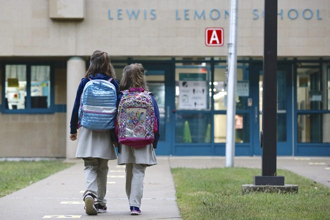 Rockford Public Schools reopened Tuesday, Sept 8, 2020. Melody Johnson, left, 9, and her sister Miranda Johnson, 6, both of Rockford, walk toward Lewis Lemon Elementary School for the first day of class.