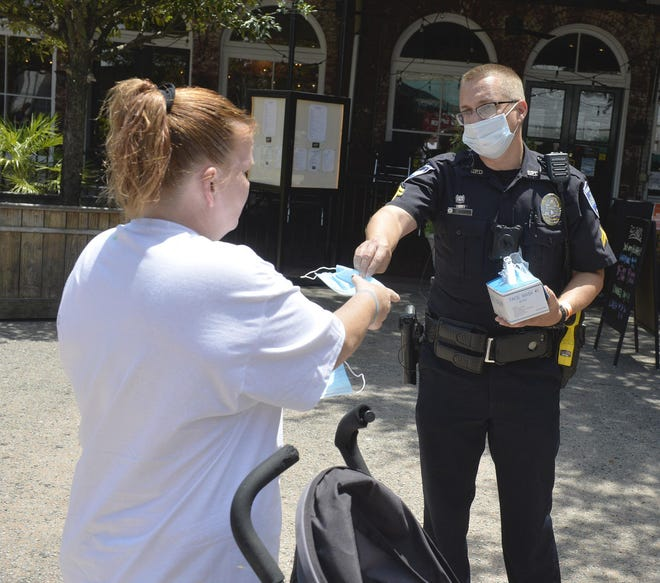 A Savannah police officer hands out face masks on July 1, the day after Mayor Van Johnson signed an emergency order mandating their use citywide in an effort against COVID-19.