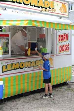 Sam Vansteenkiste of Blissfield grabs a corn dog during the 2019 Lenawee County Fair. With the 2020 fair being canceled because of the coronavirus pandemic, fair organizers held fair food drive-thru events so people could enjoy their favorite summertime snacks without the fair. A fair food walk-thru event is scheduled for this weekend, June 4-6.