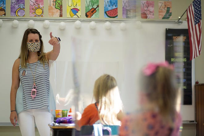ROWVA second grade teacher Katie Sexton gives the thumbs-up sign to her students as in-school classes got underway in District 208 on Monday, Aug. 24, 2020. .