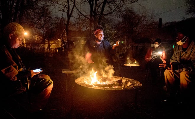 Alexander Martin speaks to the membership of the Peoria Black Artists Guild around a campfire and via cellphone during a meeting Thursday, Nov. 12, 2020 at a member's house in Peoria.