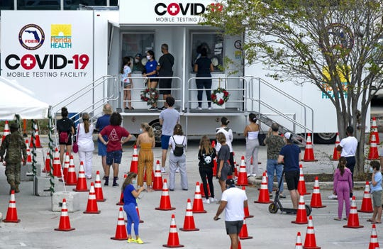 People wait in line at a COVID-19 mobile testing facility at Miami Beach Convention Center on Nov. 18, 2020.