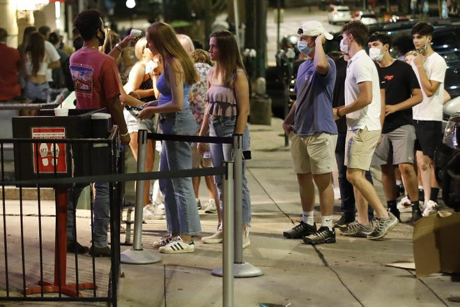 A doorman checks the temperatures of those waiting to enter the Sandbar in downtown Athens in July. Police found no violations of COVID-19 occupancy rules during recent inspections of bars.