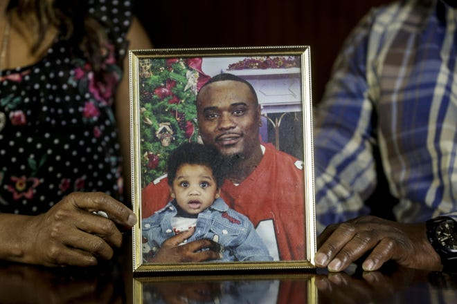 Maritza and Javier Ambler hold a photo of their son, Javier Antonio Ambler II, then 26, with his oldest son J'vaughn, then 9 months old, while at Edwards Law in Austin last month. Javier died last year while in police custody. Travis County District Attorney Margaret Moore said Wednesday the case will be handed off to her successor.