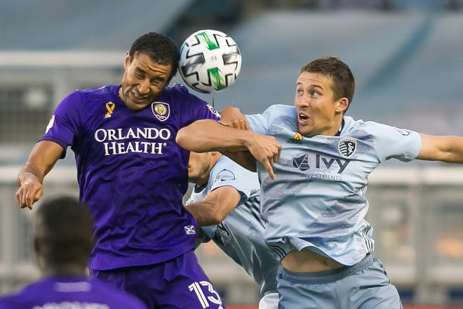 Former Sporting Kansas City defender Matt Besler, right, goes in for a header against Orlando City forward Tesho Akindele during a 2020 match. Austin FC signed 33-year old Besler, a 12-year MLS veteran, Tuesday to bolster its back line.