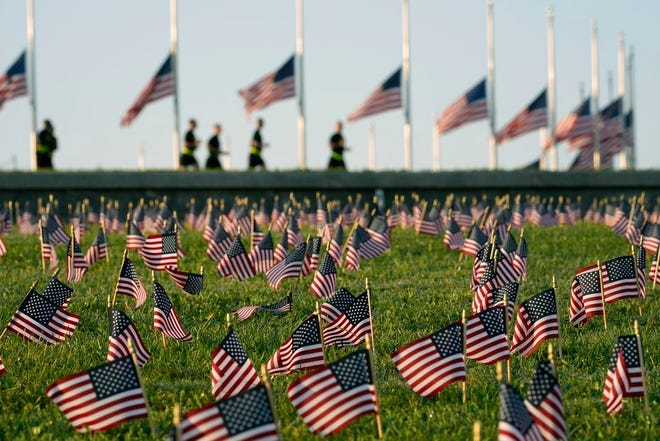 Activists from the COVID Memorial Project mark the loss of 200,000 Americans to COVID-19 by placing thousands of American flags on the grounds of the National Mall in Washington, in September. Deaths now number more than 250,000.