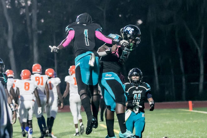 Islands High senior running back John Dickerson IV (1) and sophomore tackle Jordan Carter-Brown (51) celebrate after the game's first score against Johnson High last week at Islands Stadium.