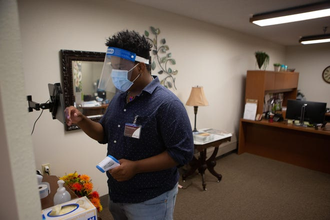 Christopher Wells, security at Aldersgate Village Life Plan Community, goes through the steps of screening in a vistor Saturday afternoon. Only preauthorized vistors are allowed at the community and must be screened, wear a name tag, mask and face shield while visiting.