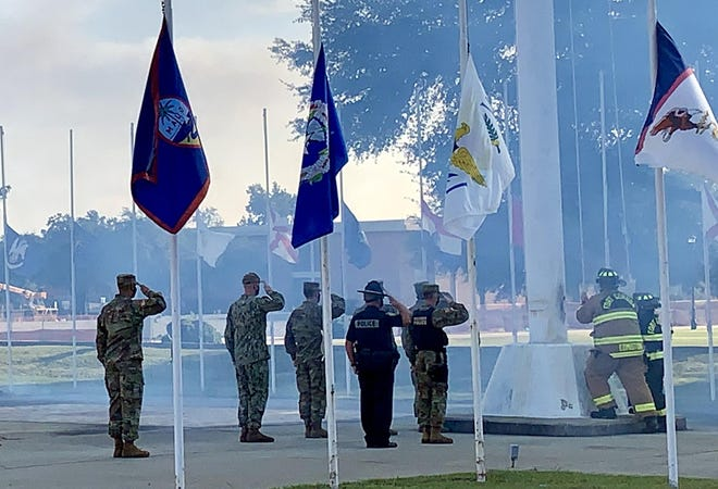 Fort Gordon military and first responders salute the U.S. flag as it is lowered to half-staff following a cannon fire in remembrance of 9/11 during a ceremony outside the U.S. Army Signal Corps Museum Friday.