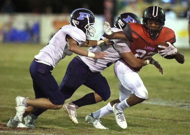 Augusta Christian's Terrence Vandiver, right, tries to escape a pair of Pinewood defenders  during football action at Augusta Christian in Martinez, Ga., Friday evening October 9, 2020