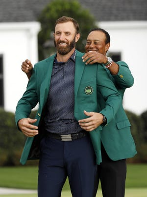 Tiger Woods puts the green jacket on Dustin Johnson after his Masters Tournament victory Sunday afternoon. Johnson set the tournament scoring record at 20-under 268 to win by five shots.