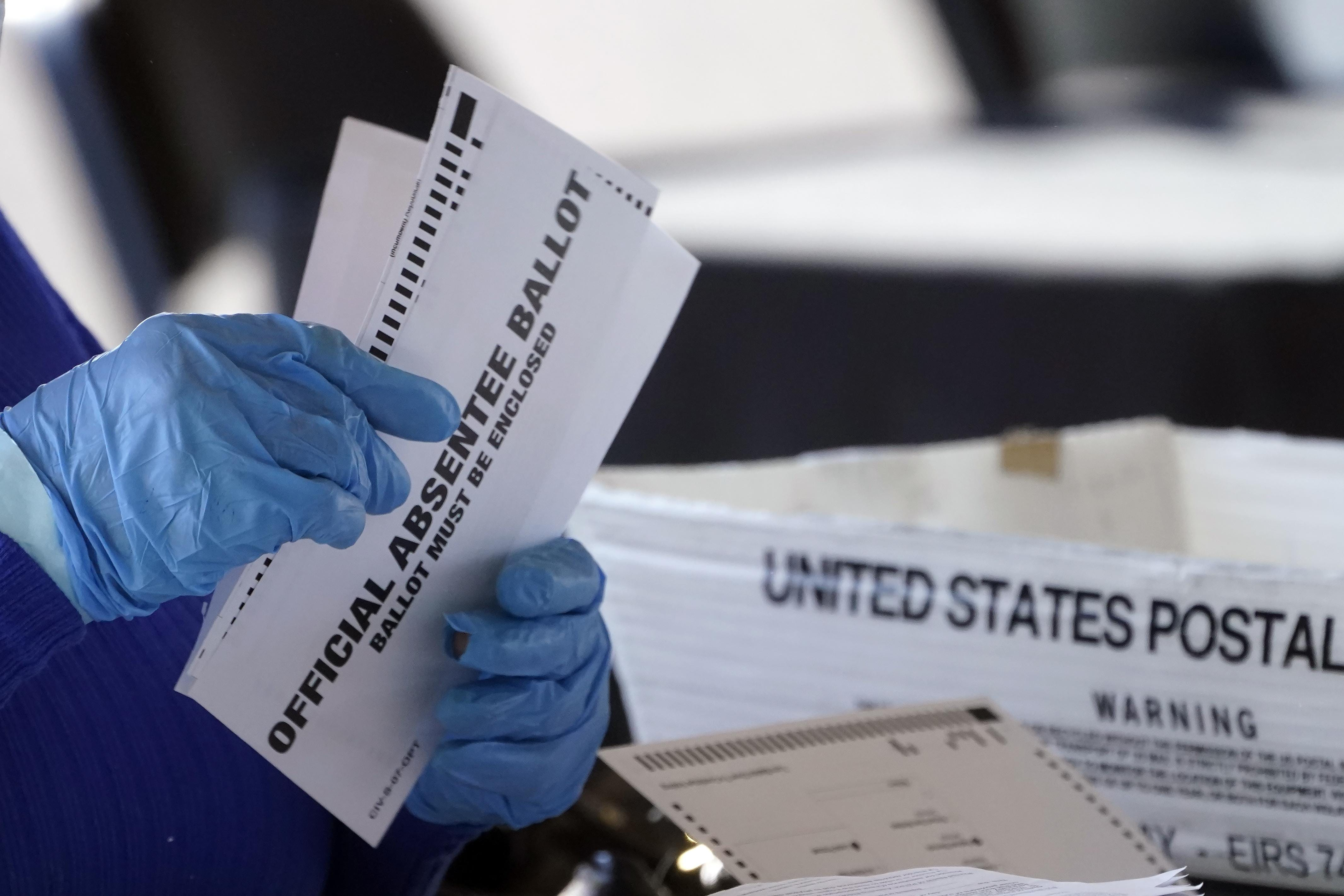 A worker at the Fulton County Board of Registration and Elections works to process absentee ballots at the State Farm Arena Monday, Nov. 2, 2020, in Atlanta.