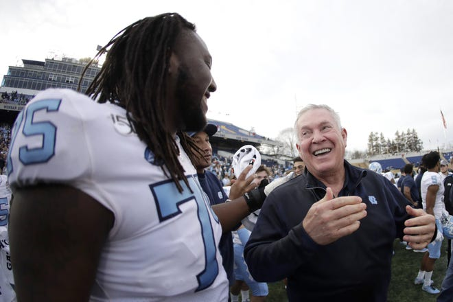 North Carolina offensive lineman Joshua Ezeudu, left, and coach Mack Brown celebrate the Tar Heels' blowout of Temple at the Military Bowl in December 2019.
