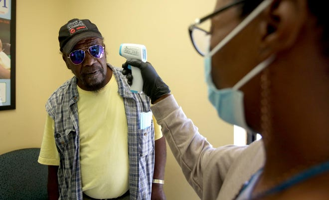 James Norris has his temperature checked by Phyllis Williams at the Cleveland County Rescue Mission in this Star file photo.