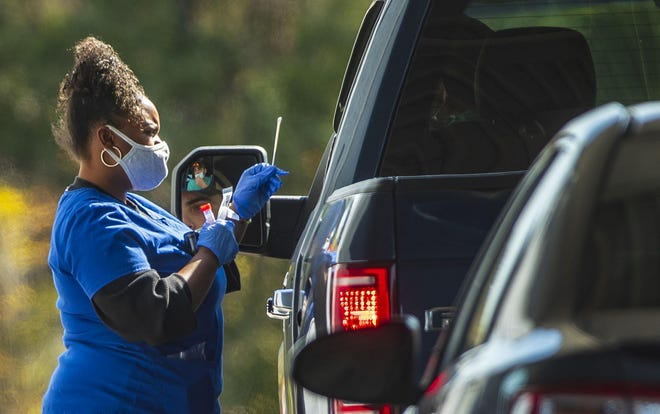 As coronavirus cases rise in Texas, a health care worker administers a COVID-19 test at a drive-thru site at Family Emergency Room in Cedar Park on Nov. 11.