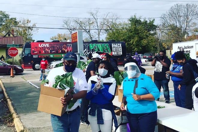 Volunteers distribute food boxes during a Black Voters Matter stop in Augusta Wednesday.