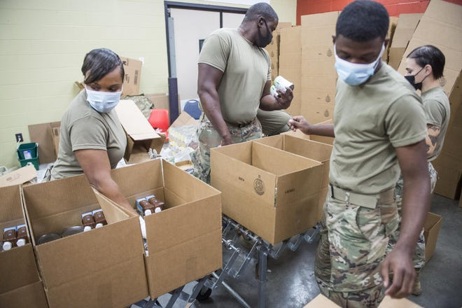 Georgia National Guard soldiers pack boxes of food at the Golden Harvest Food Bank in Augusta, Ga., Tuesday morning December 1, 2020.