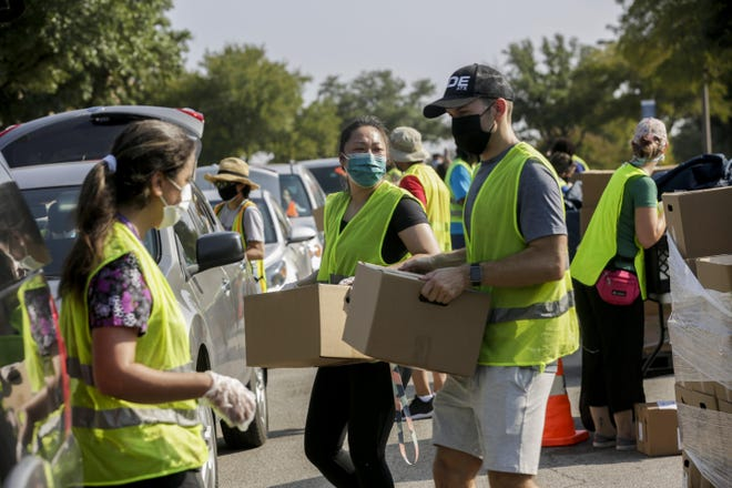 Employees from Central Texas Food Bank load disaster relief boxes into cars during a mobile food pantry in August at Austin Community College's Riverside campus. Families' need for food and the rates of coronavirus spread are directly related, University of Texas Dell Medical School researchers found.