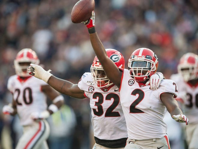 Georgia inside linebacker Monty Rice (32) and Georgia defensive back Richard LeCounte (2) celebrate LeCounte's fumble recovery at Jordan-Hare Stadium in Auburn, Ala., on Saturday, Nov. 16, 2019.