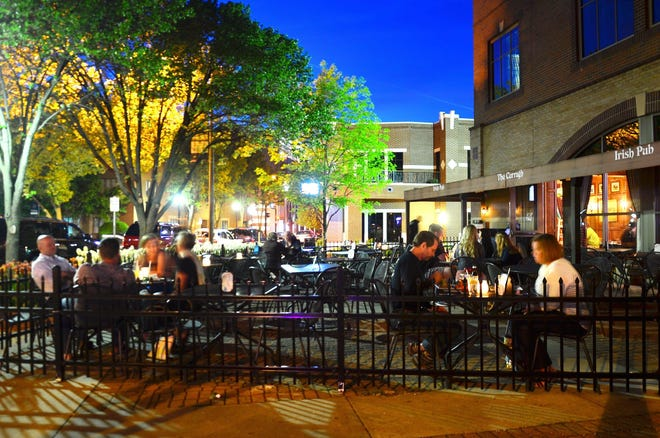 In this 2014 file photo, diners eat on the outdoor patio at Holland's Irish pub The Curragh. The Holland City Council approved the temporary waiver of sidewalk cafe renewal fees at its Wednesday meeting.