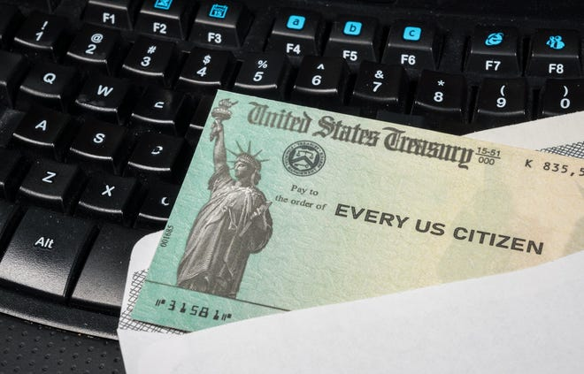 Federal government-issued check lying on a computer keyboard.