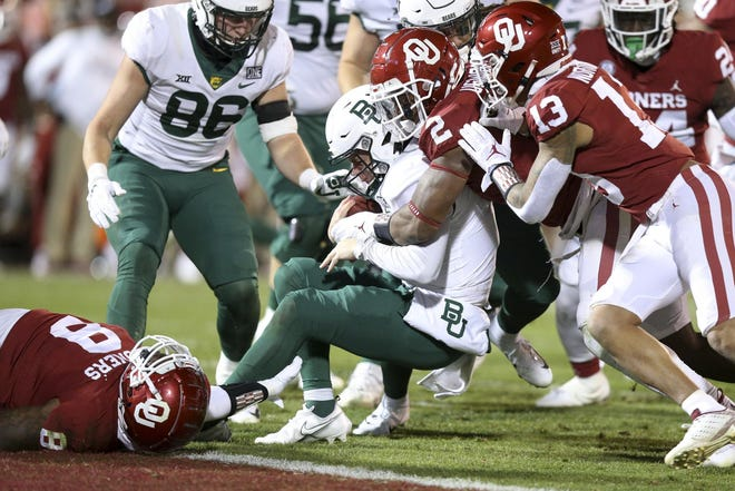Oklahoma defensive back Tre Norwood (13), are among those teaming up to tackle Baylor quarterback Charlie Brewer (5) on a game held Dec. 5, 2020 in Norman, Okla. Norwood, who was named the defensive MVP in Wednesday's Cotton Bowl win against Florida, announced on Friday that he is foregoing his senior year at Oklahoma and declare for this spring's NFL Draft.