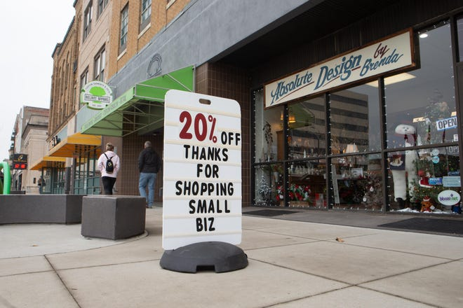 A sign outside of Absolute Design by Brenda in Topeka encourages customers to shop local.