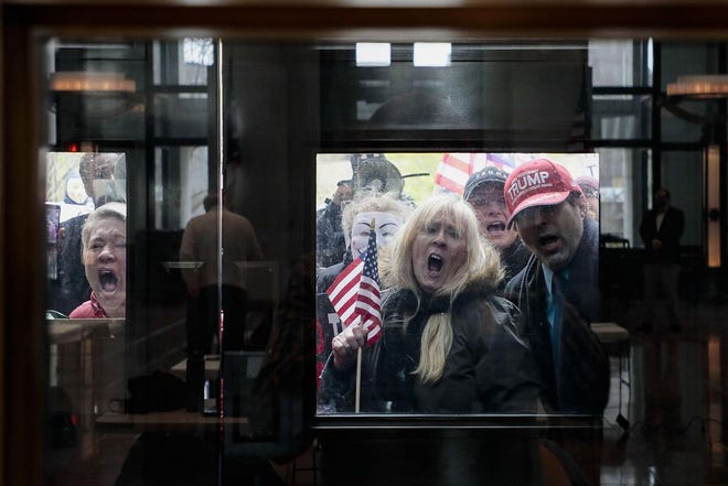 Former Ohio Senate candidate Melissa Ackison, left, was among the vocal protesters outside the Statehouse atrium on April 13 taking issue with coronavirus stay-at-home orders from the administration of Republican Gov. Mike DeWine.