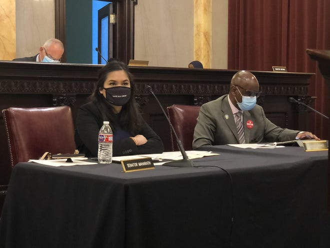 """State Sen. Tina Maharath, D-Canal Winchester, left, wears a mask that says """"hate is a virus"""" during a committee hearing in late June."""