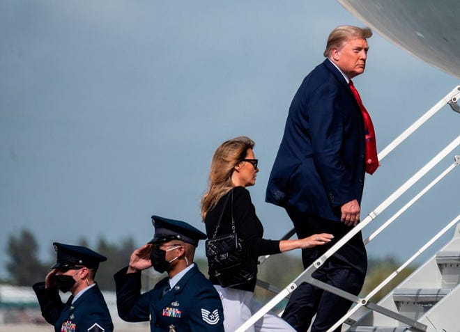 President Donald Trump and first lady Melania Trump board Air Force One as they prepare to leave West Palm Beach, Florida, on Wednesday. The president has kept a low profile since his election loss but has worked feverishly behind the scenes in an effort to overturn the election results.