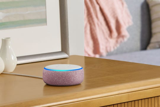 An Amazon Echo Dot smart speaker on a side table.