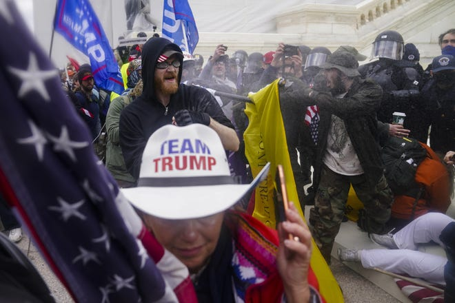 In this Jan. 6, 2021, file photo, Trump supporters try to break through a police barrier at the Capitol in Washington. The U.S. registered its highest deaths yet from the coronavirus on the same day as a mob attack on the nation's capitol laid bare some of the same, deep political divisions that have hampered the battle against the pandemic.