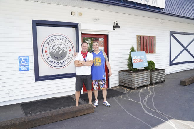 Co-owners of Pinnacle Emporium, a cannabis provisioning center in Addison, are Michael Silver, left, and Erik Watkins. The two are pictured in front of the Addison business during its July 2020 grand opening.