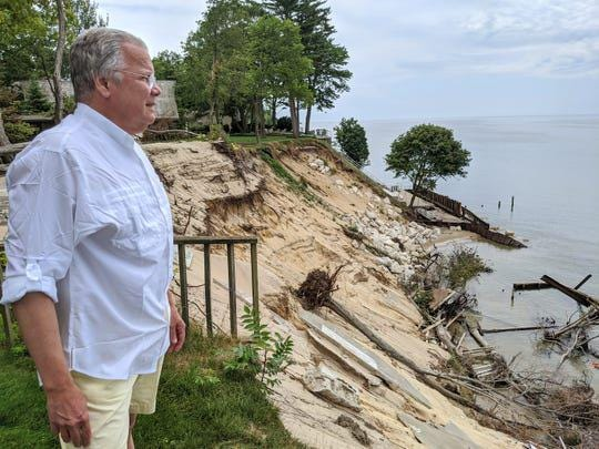 Park Township's Tim Lathe looks out on Lake Michigan while surrounded by the major shoreline erosion destroying his and his neighbors' decks, stairways, sea walls and other shoreline infrastructure.