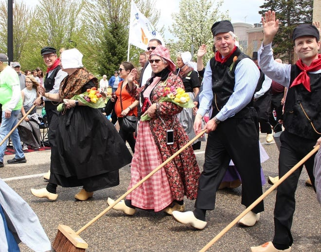 Gov. Rick Snyder, second from right, and Lt. Gov. Brian Calley, right, join Tulip Time Executive Director Gwen Auwerda, center, and others in sweeping the streets prior to the 2018 Volksparade. Tulip Time 2021 will take place May 1-8.