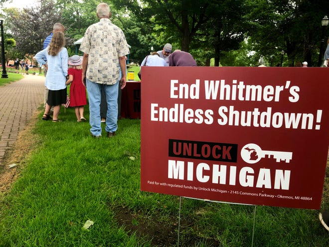 """A petition drive called """"Unlock Michigan"""" has gained momentum in the state since being launched earlier this summer. Supporters sign the petition Aug. 1 at Holland's Centennial Park before a law enforcement rally."""