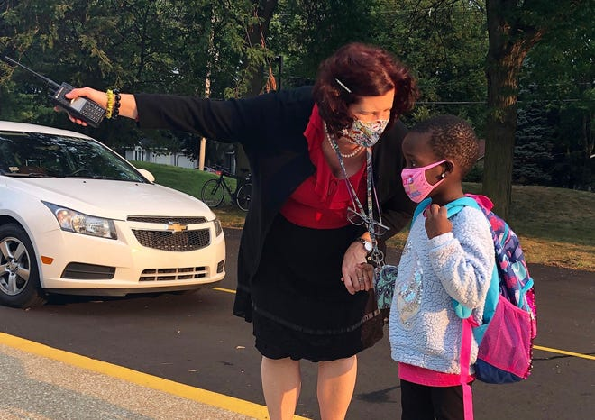 Holland West Elementary principal Kathleen Ramirez points a student to her teacher and classmates on Holland Public Schools' first day back in the classroom Wednesday, Aug. 26. HPS families are asked to submit a learning model choice for the second semester by Nov. 1.