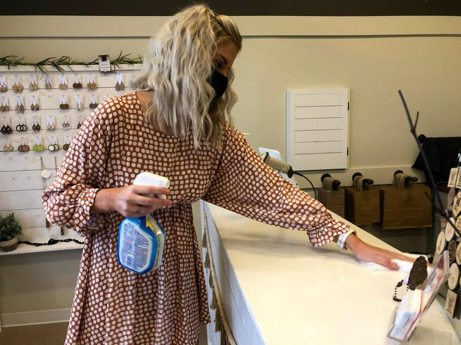 Heather TenHarmsel, owner of The Poppy Peach, wipes down a counter with cleaner Thursday, Dec. 17, in preparation for her first customers of the day.