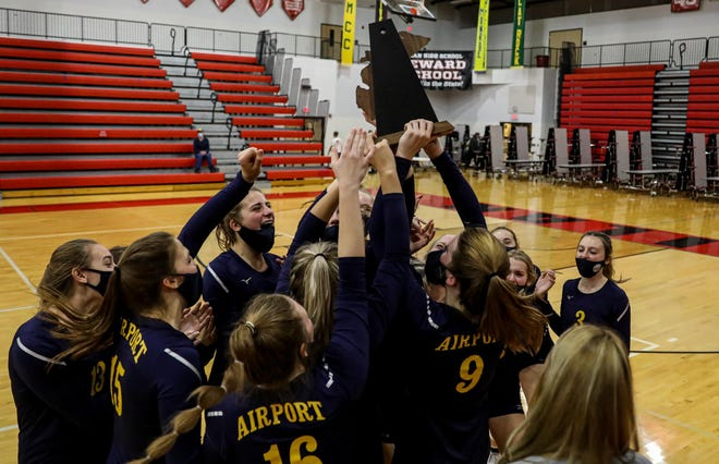 Airport's volleyball team celebrates with the District championship trophy last season.