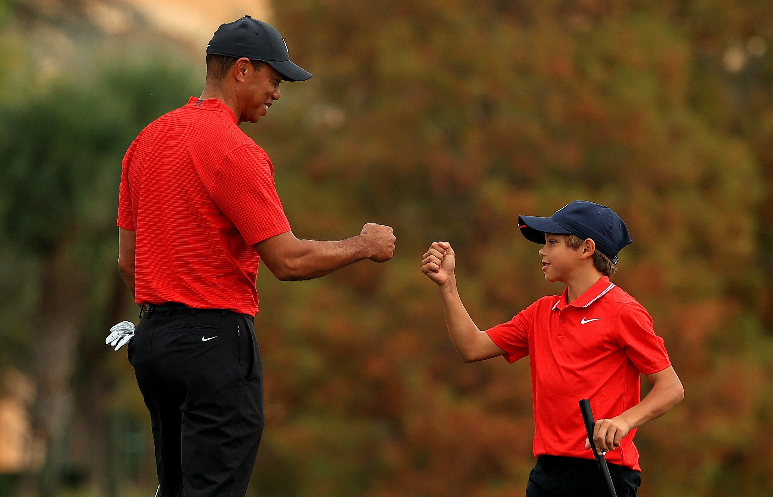 Tiger Woods fist bumps his son Charlie while playing golf together for the PNC Championship.
