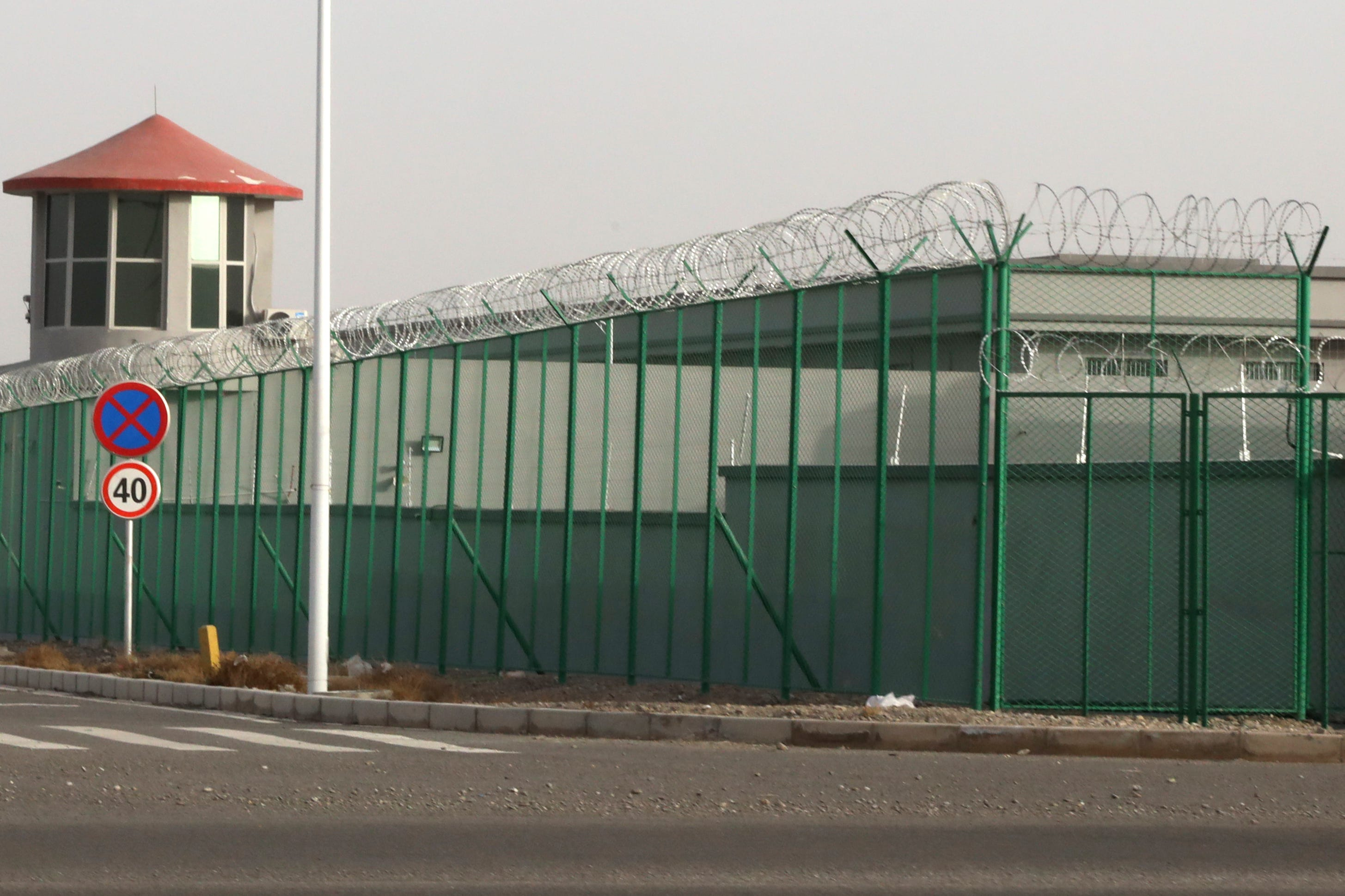A guard tower and barbed wire fence surround a detention facility in the Kunshan Industrial Park in Artux in western China's Xinjiang region in 2018. A small core of international lawyers and activists are prodding leading Olympic sponsors to acknowledge China's widely reported human-rights abuses against Muslim Uyghurs, Tibetans and other minorities.