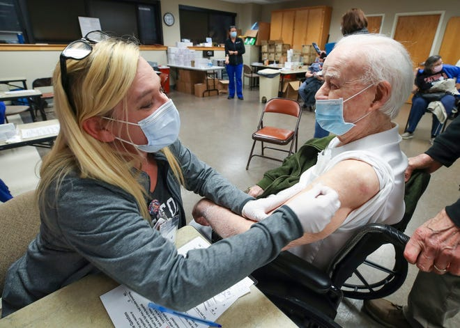 Nurse April Israel administers the second dose of COVID-19 vaccine to Don Robinson, 105, at Norton Audubon Hospital in Louisville, Ky., on Feb. 12. Robinson was 3 years old when the Spanish flu killed 675,000 people in the USA. Robinson hopes to visit with family in Idaho, California and Florida he hasn't seen since the coronavirus pandemic started.