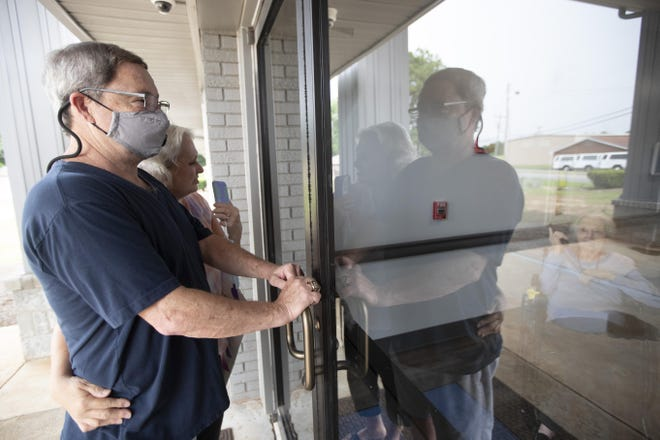 Southern Pines nursing home resident Shirley Campbell visits with her daughter, Margie Price, and son-in-law, Ken, through a glass door in Warner Robins, Ga., on June 26.