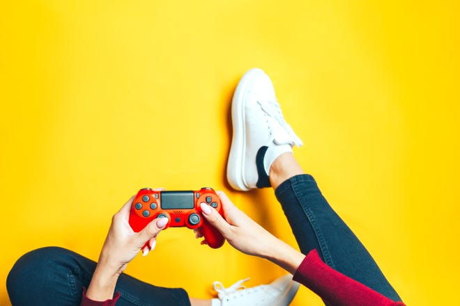Person sitting on a floor playing video games.