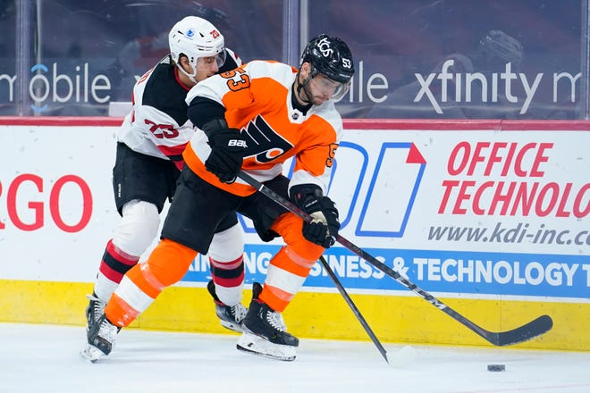 Philadelphia Flyers' Shayne Gostisbehere, right, keeps the puck away from New Jersey Devils' Michael McLeod during the first period of an NHL hockey game, Tuesday, March 23, 2021, in Philadelphia. (AP Photo/Matt Slocum)