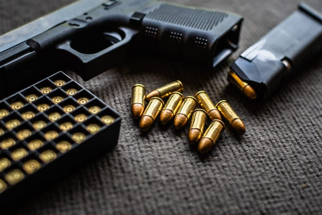 An unloaded gun with bullets lying near a loaded magazine and container of more bullets