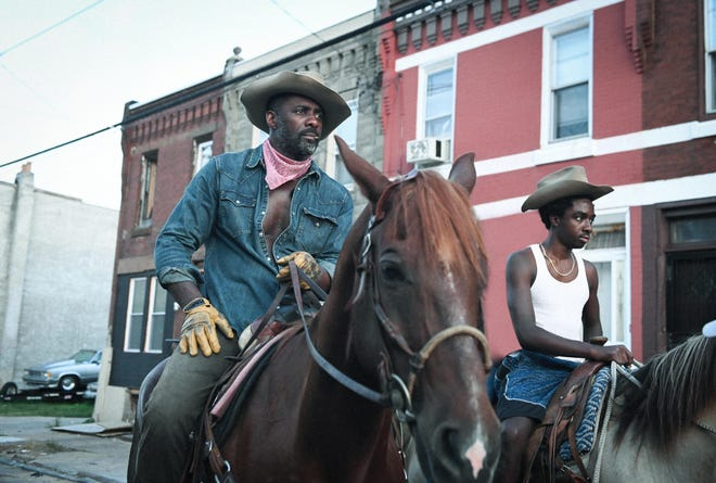 "Idris Elba, left, and Caleb McLaughlin in a scene from ""Concrete Cowboy."""