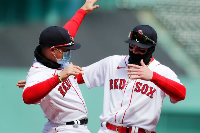 Boston Red Sox's Enrique Hernandez, left, and Alex Verdugo react during introductions before an opening day baseball game against the Baltimore Orioles, Friday, April 2, 2021, in Boston. Verdugo started the first three games of the season at three different defensive positions.