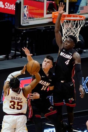 Cleveland Cavaliers forward Isaac Okoro (35) shoots as Miami Heat guards Tyler Herro (14) and Victor Oladipo (4) defend during the second half of an NBA basketball game Saturday, April 3, 2021, in Miami. [Marta Lavandier/Associated Press]